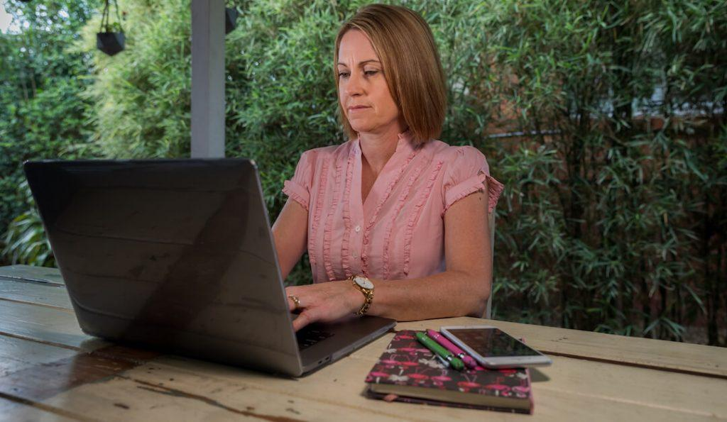 Kerri McConnel - on macbook Headshot